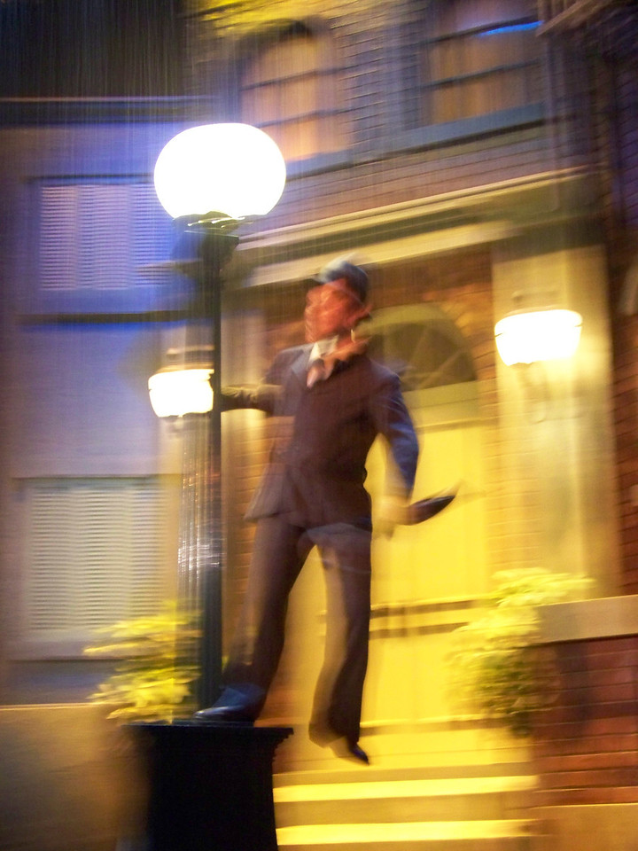 Here's Gene Kelly in Singing in the Rain.<br /> As in most of the rides with audio-animatronic figures, the lighting inside is very low.  With the motion of the vehicle, getting clear shots is difficult, but you get the general idea.<br /> [Disney's Hollywood Studios - Great Movie Ride]