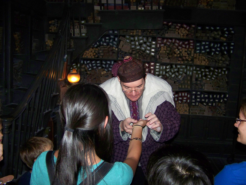 We waited over an hour to enter Ollivanders Wand Shop, where they put on a little show.  They let in about 15 to 20 people at a time, and then Mr. Ollivander's associate, seen here, selects someone and helps them choose their wand--or more accurately, finds the wand that wants to choose them.  Was it worth the wait?  Not really.  From the descriptions I had read online, I thought this would be more impressive.  Of course, if you or someone in your party is the selectee, then that probably makes a difference!<br /> [Universal Islands of Adventure - Wizarding World of Harry Potter]