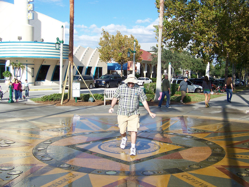 At least one big kid (Pat) had to get in on the fun of dodging the water jets, too!  Note the design on the ground under the fountain--it's a huge compass rose.<br /> [Celebration, Florida]