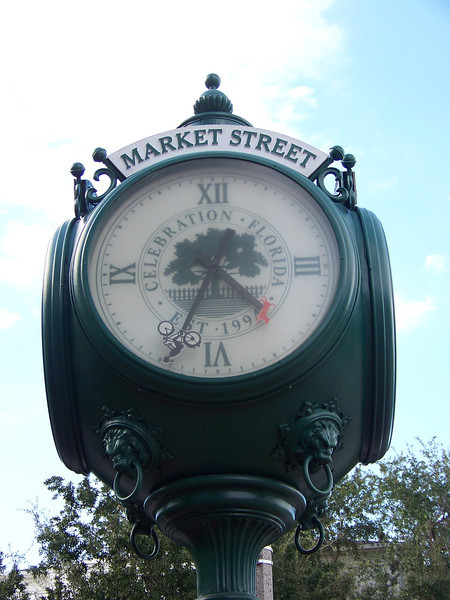 A clock on the street in the town center.  Note the (upside-down) bicycle and dog at the ends of the clock's hands.<br /> [Celebration, Florida]