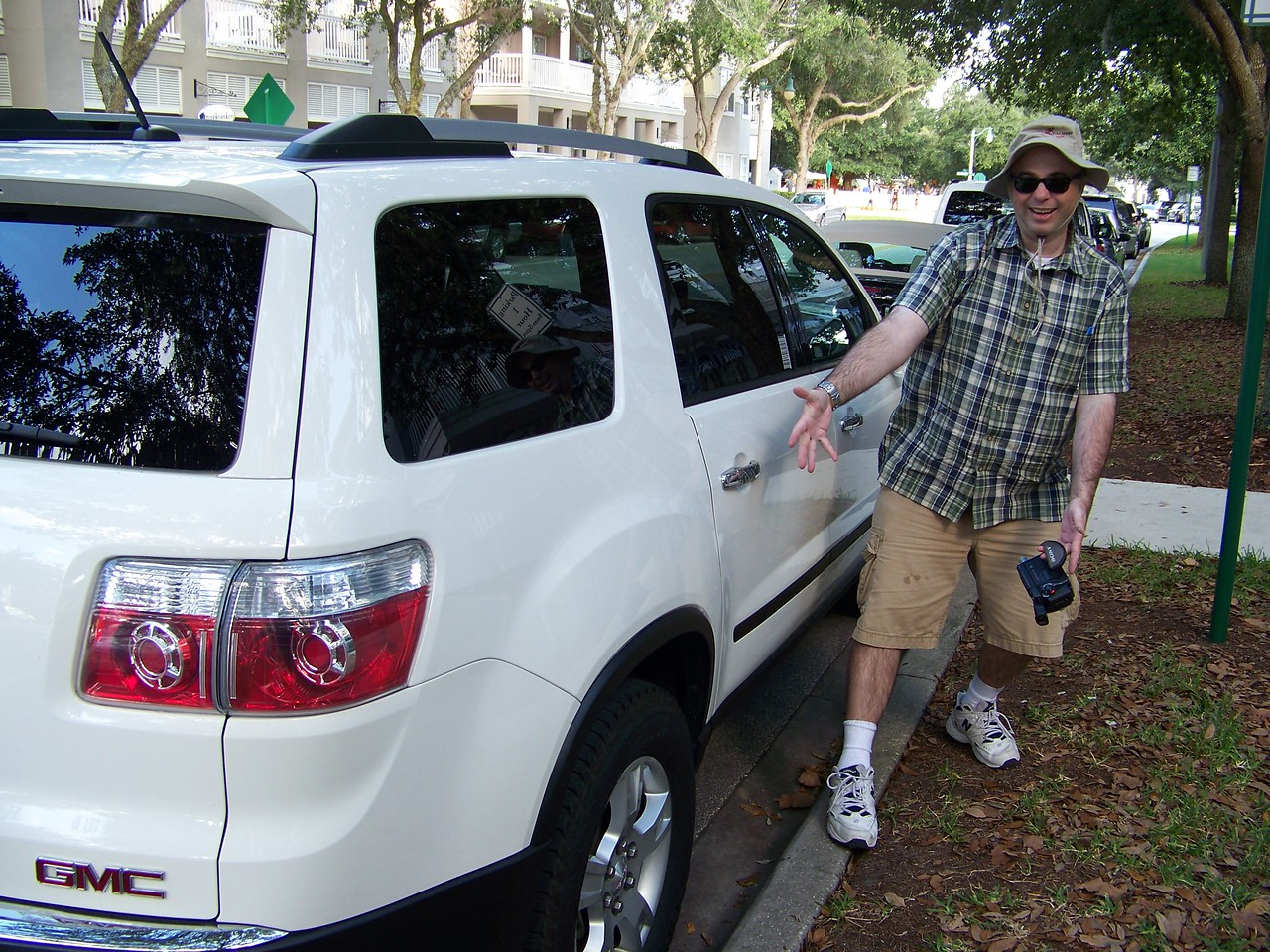 Pat shows off the fantastic parallel-parking job he did with the GMC Acadia we rented, despite the tight parking space in Celebration's town center.<br /> [Celebration, Florida]