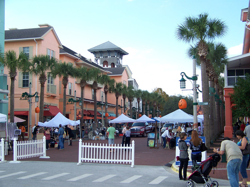 We walked through the arts and crafts fair, but didn't buy anything.  This is the opposite end of the block from the previous shot.  The tower we couldn't figure out can be seen behind the pink building at left.<br /> [Celebration, Florida]