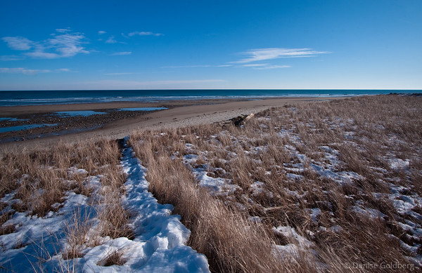 snow, sand, ocean in the distance
