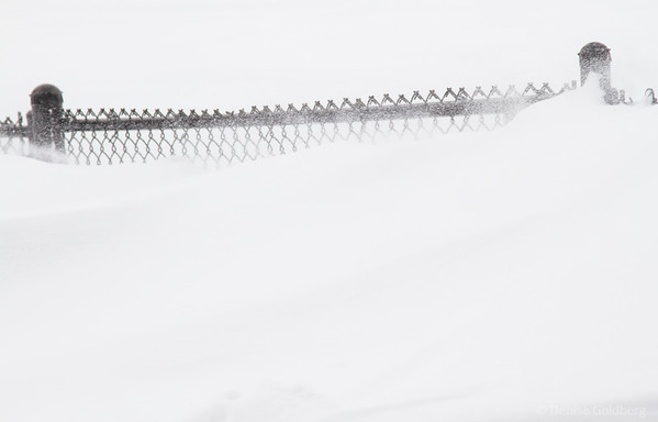 a fence buried in snow