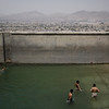 Boys swim in the pool nestled atop the highest peak in the Wazir Akbar Khan district of Kabul on Monday, July 20, 2009. Years ago, under Taliban rule, the pool was drained and used only for executions by stoning.
