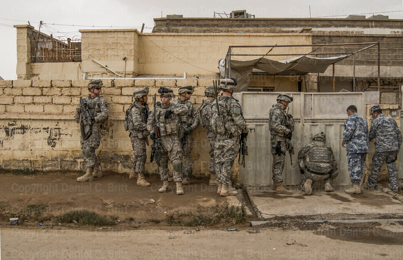 United States soldiers gather outside a home in Bayji before raiding it to search for insurgents and weapons on Monday, March 2, 2009.