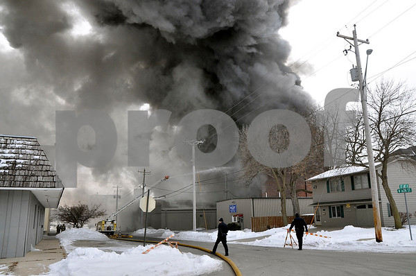 -Messenger photo by Joe Sutter<br /> <br /> Fort Dodge police adjust barricades along Sixth Street, while down the street Fort Dodge's Areal One fire truck, a smaller and older model than the ladder truck used in front, trains a stream of water on the burning warehouse. Buildings were evacuated for two blocks to the east where smoke was blowing, due to the smoke.