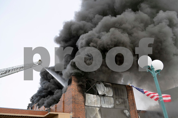 -Messenger photo by Chad Thompson<br /> <br /> Fort Dodge firefighters confront thick black smoke at a burning warehouse, framed by the lamp post and flagpole along Central Avenue. Much of the ceiling and wall has collapsed in this photo.