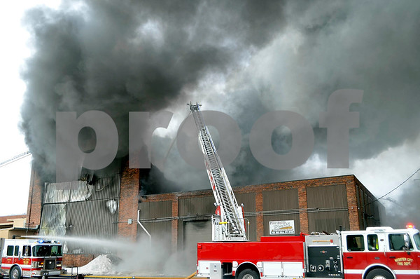 -Messenger photo by Chad Thompson <br /> <br /> The Webster City ladder truck, shown here, joins Fort Dodge fire trucks in battling a huge warehouse fire at the corner of Central Avenue and 15th Street. Two blocks to the east were evacuated due to toxic smoke coming from burning tires and insulation inside the building