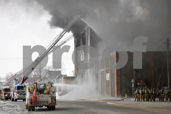 -Messenger photo by Joe Sutter<br /> <br /> The Webster City Ladder truck, closer, and Fort Dodge ladder truck provide water from high up, as firefighters convene at the scene to the right. The warehouse was in the same building as the Fort Dodge school baseball building the Bat Cave.