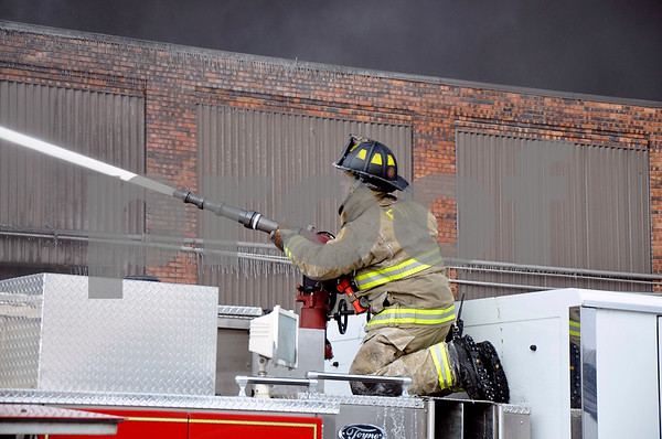 -Messenger photo by Joe Sutter<br /> <br /> A Fort Dodge firefighter trains a water jet on the burning warehouse Monday.