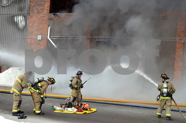 -Messenger photo by Chad Thompson<br /> <br /> A group of firefighters adjust air packs next to a collection of tools as they prepare to engage the fire.