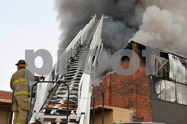 -Messenger photo by Chad Thompson<br /> <br /> A Fort Dodge firefighter prepares to climb the ladder truck to combat the warehouse fire Monday. Fire crews were on scene by 1:10 p.m., and were later joined by a similar ladder truck from Webster City.