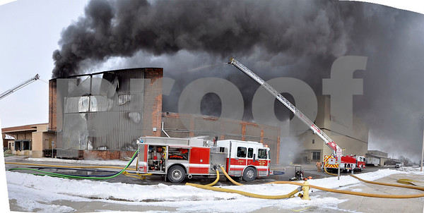 -Messenger photo illustration by Joe Sutter<br /> <br /> Fort Dodge and Webster City firefighters line up along Central Avenue to fight a massive warehouse fire, in this image made from multiple photos. Assistant Fire Chief Lenny Sanders said crews will be on scene for hours as tires inside continue burning.