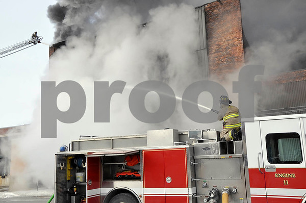 -Messenger photo by Joe Sutter<br /> <br /> Fort Dodge firefighters battle the blaze from the ground and from high above the burning warehouse's wall on the ladder truck, at left.