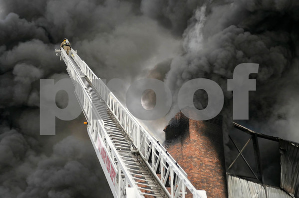 -Messenger photo by Chad Thompson <br /> <br /> A Fort Dodge firefighter works atop Ladder One at a large warehouse fire Monday afternoon. Tires and foam insulation inside the building contributed to the thick black smoke.
