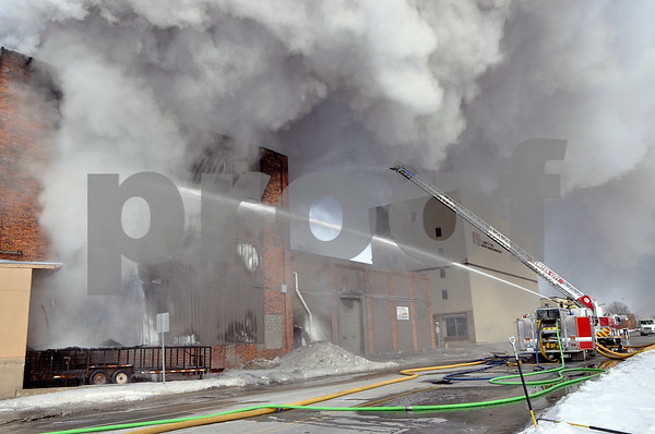 -Messenger photo by Joe Sutter<br /> <br /> As a Fort Dodge firefighter trains water on the fire from the ground, the Webster City ladder truck assists in the background. Fire crews traded off to help cope with the extremely cold weather.