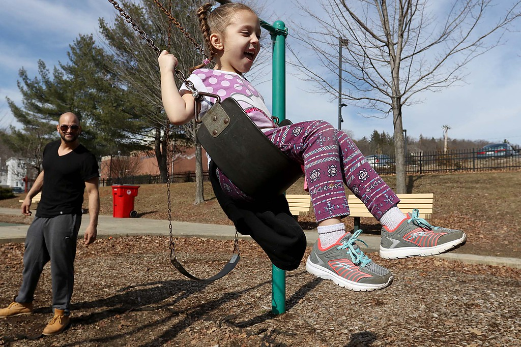 . Luis Marquez give Jaeda Martinez, 6, of Fitchburg a push on the swings at Green Street Park in Fitchburg as they enjoyed getting out in the temperatures that got into the 70\'s, February 21, 2018. SENTINEL & ENTERPRISE/JOHN LOVE