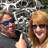 Warren Shaw, left, and his girlfriend Mary Jane McArdle, right, pose in front of one of the elk anter arches in the heart in Jackson Hole, Wyoming.
