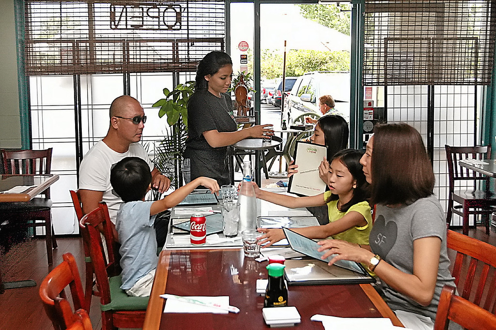 . A family of five settles in for lunch at Wasabi Tapas in Capitola\'s Brown Ranch Marketplace. (Dan  Coyro -- Santa Cruz Sentinel)