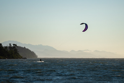 sunset kite surfing in the sea with mountains in the background