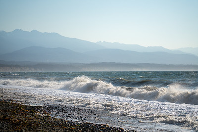 waves crashing on the beach with hazy mountains in the background