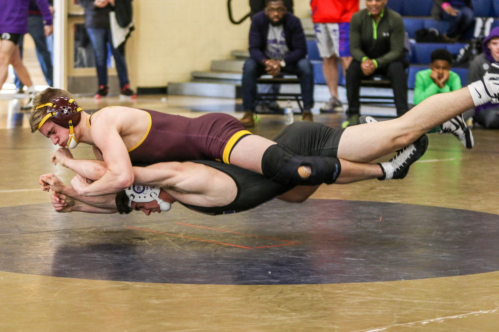 Jack Brown of Gonzaga College High School in Washington and Charlie Brenner of Bishop McNamara High School in Forestville go airborne and horizontal as Brown attempts to break Brenner's hold. Brenner won third place by a score of 7-0.