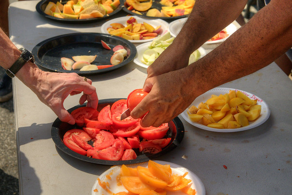 A vendor slices some fresh tomatoes at the Dupont Circle FRESHFARM Market, a farmers' market with produce and baked goods from local farms, located at 20th Street NW in Dupont Circle in Washington, DC,  on Sunday, August 17, 2014. Copyright 2014 Jason Barnette