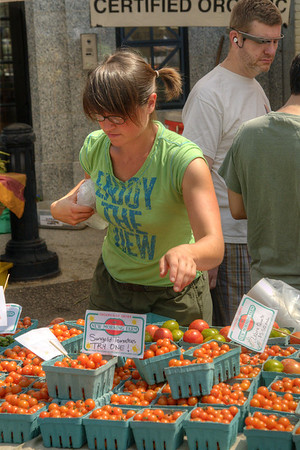A woman looks for a basket of tomatoes at the Dupont Circle FRESHFARM Market, a farmers' market with produce and baked goods from local farms, located at 20th Street NW in Dupont Circle in Washington, DC,  on Sunday, August 17, 2014. Copyright 2014 Jason Barnette