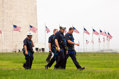 Members of the Fire Department Technical Rescue Team patrol the area around the Washington Monument while ropes are attached to the top of the Monument, on the National Mall, in Washington DC, Tuesday, Sept. 27, 2011, from which four people will rappel down the sides to survey the extent of damage sustained from the August 23 earthquake. (Photo by Jeff Malet)