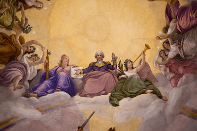 "In the central group of the fresco, Brumidi depicted George Washington rising to the heavens in glory, flanked by female figures representing Liberty and Victory/Fame. A rainbow arches at his feet, and thirteen maidens symbolizing the original states flank the three central figures. (The word ""apotheosis"" in the title means literally the raising of a person to the rank of a god, or the glorification of a person as an ideal; George Washington was honored as a national icon in the nineteenth century.)"