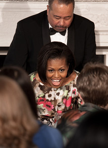 Michelle Obama takes her seat after paying tribute to her own mother, Marian Robinson, at a Mother's Day tea at the White House in Washington DC on May 7, 2010. The event included former first lady Rosalynn Carter and granddaughter, Sarah Carter; President Richard Nixon's daughter Tricia Nixon Cox; and President Dwight D. Eisenhower's granddaughters Susan and Anne Eisenhower, along with young women who participate in Mrs. Obama's mentoring program, spouses and mothers of service members, and Vice President Joe Biden's wife, Jill. (Photo by Jeff Malet)