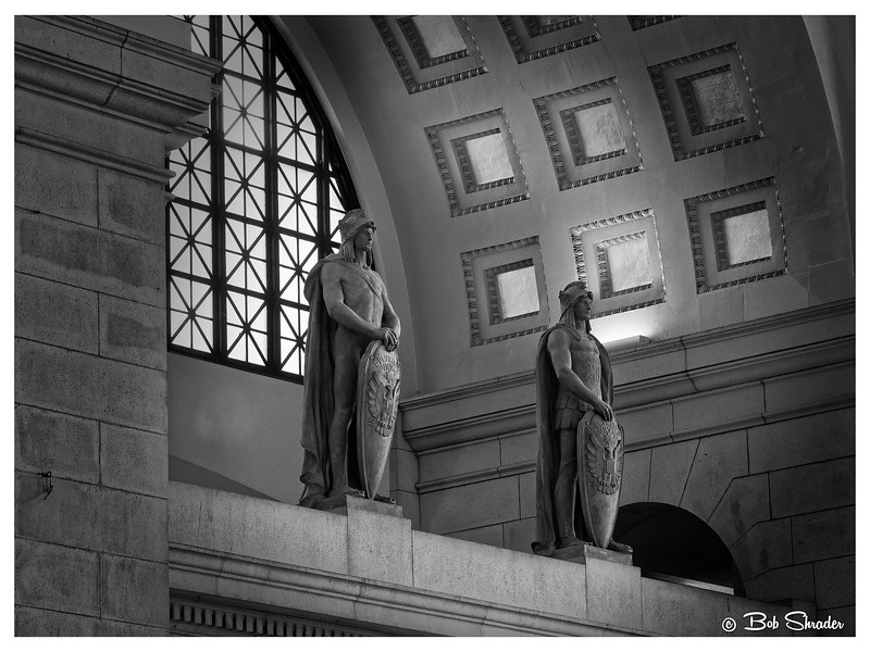"Black & white film-look  rendering of part of the decorative art in Union Station, a busy landmark in Washington, DC. These two  statue are amongf 36 Roman legionnaires around the interior. The facility, completed in 1908, was designed by architect Daniel Burnham in Beaux-Arts style from classic Roman Baths. American sculptor Louis Saint-Gaudens designed statues of Roman soldiers to complement Burnham's design. Saint-Gaudens submitted a plaster cast prototype to railroad officials. But the model was portrayed in garments  the legionaires actually wore -- or didn't wear -- in ""commando"" mode with no covering of the male penis. A long dispute ensued. A compromise resulted in including a shield in a strategic place to protect the public from having to view the body part that every male possesses. Raw development in DxO PhotoLab with lens correction in DxO ViewPoint 3. Post processing  in DxO FilmPack 5 (Ilford Pan 100) and Alien Skin Exposure X4."