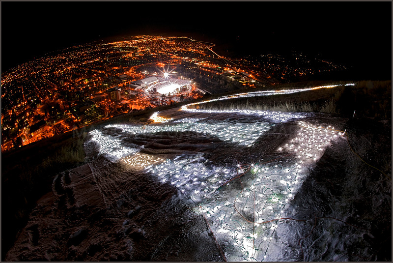 "The ""M"" and Washington Grizzly Stadium<br /> <br /> The ""M"" illuminated with Christmas lights looking over Missoula and the Washington Grizzly Stadium during the Montana Grizzly and Norther Iowa game on Friday December 9th, 2011 when the Grizzlies won 48-10 over Northern Iowa and advance to the next round of the playoffs.<br /> <br /> Please note: The watermark in this image will not be in the final printed photo."
