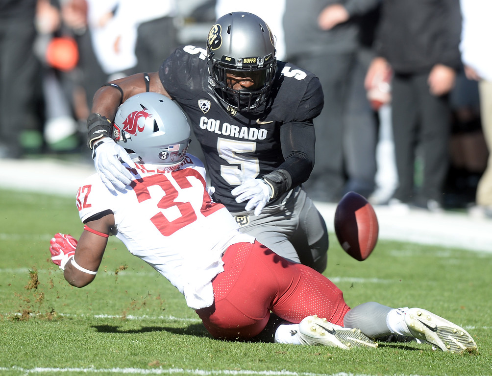 . BOULDER, CO: November 10: Davion Taylor, of CU, separates the ball from James Williams, of WSU, during the game with Washington State. (Photo by Cliff Grassmick/Staff Photographer)
