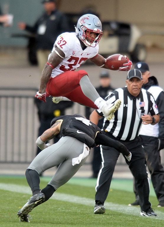 . BOULDER, CO: November 10: James Williams, of WSU, hurdles Dante Wigley, of Colorado, during the game with Washington State. (Photo by Cliff Grassmick/Staff Photographer)
