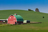 A red barn in the rolling hills of the Palouse region of Washington, USA.