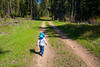 Kittitas, Teanaway - Little boy walking through forest on an old logging road