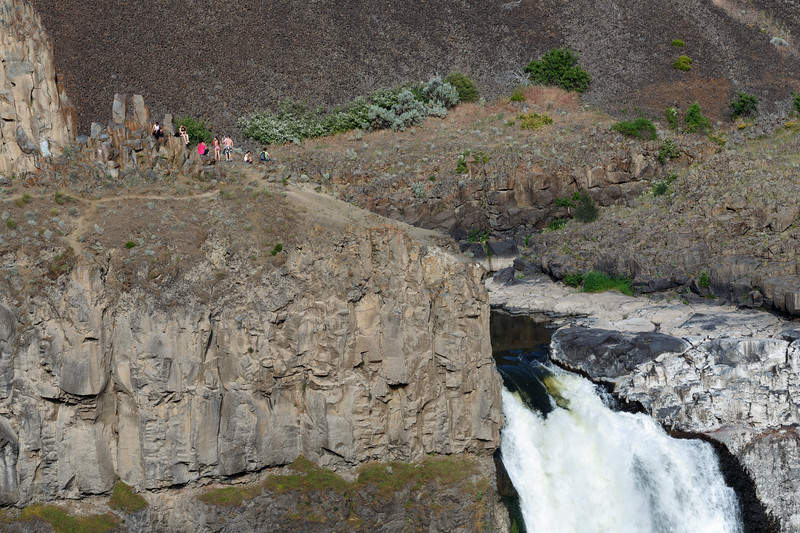 Palouse, Palouse Falls - Group of people perched precariously on a ledge above Palouse Falls