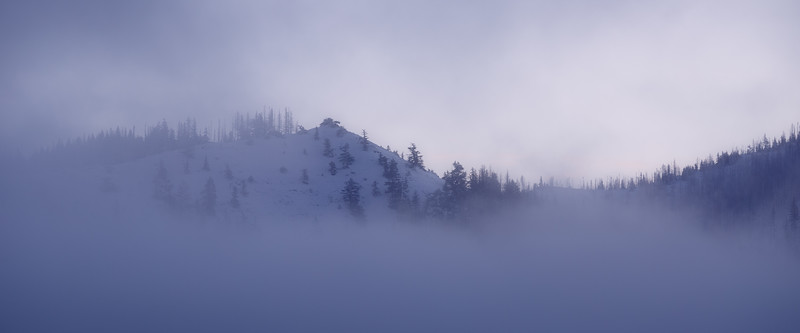 Kittitas, Blewett Pass - Clouds and fog on snowy mountain hillside at sunrise