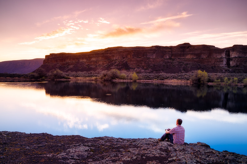 Columbia, Sun Lakes Dry Falls - Man sitting on shore of lake at sunset