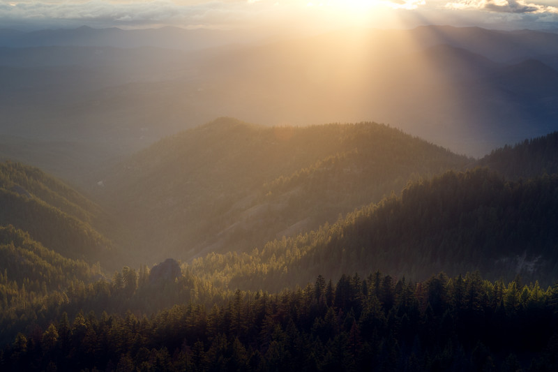 Kittitas, Red Top - Sunbeams illuminating a rock above a forested valley from high above