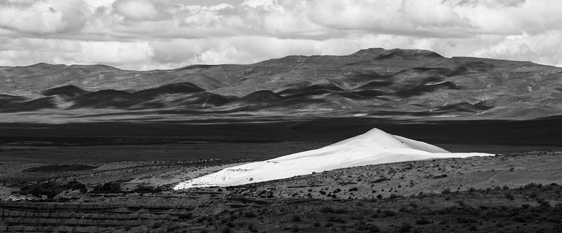 Columbia, Mattawa - Distant sand dune lit by sun through clouds, black and white