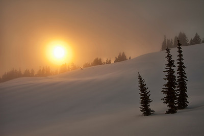Right before the sun set, the clouds and fog covered all of the views.  I decided to head down, and all of the sudden a fireball revealed itself and bathed the world in a gorgeous golden glow.  The side lighting also helped reveal the patterns in the snow as well.