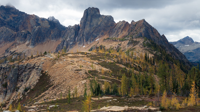 Rainy Pass, Cutthroat Pass - Ridgeline leading towards Cutthroat Peak above Cutthroat Pass with larch trees and hikers taking in the view