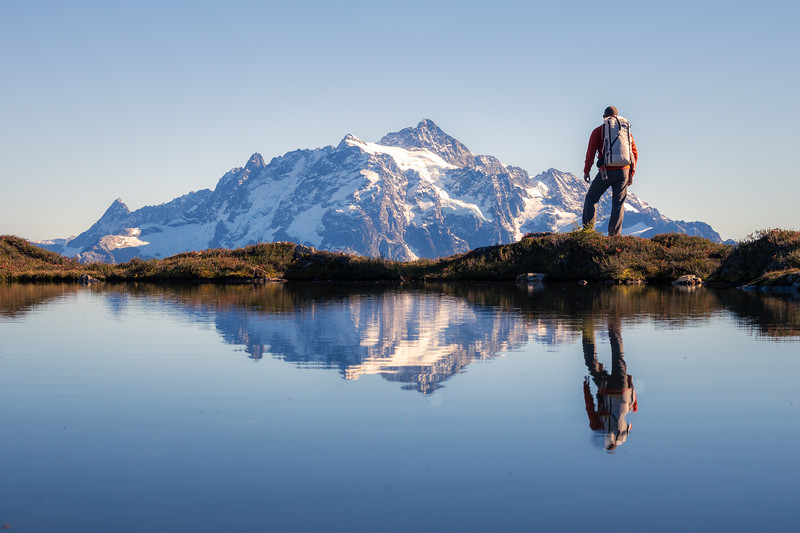Whatcom, Yellow Aster Butte - Hiker pausing to look at Mt. Shuksan reflected in tarn