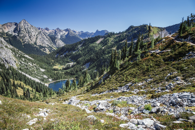 Rainy Pass, Maple Pass - View of the Lake Ann basin on a summer day with a lone hiker on the trail