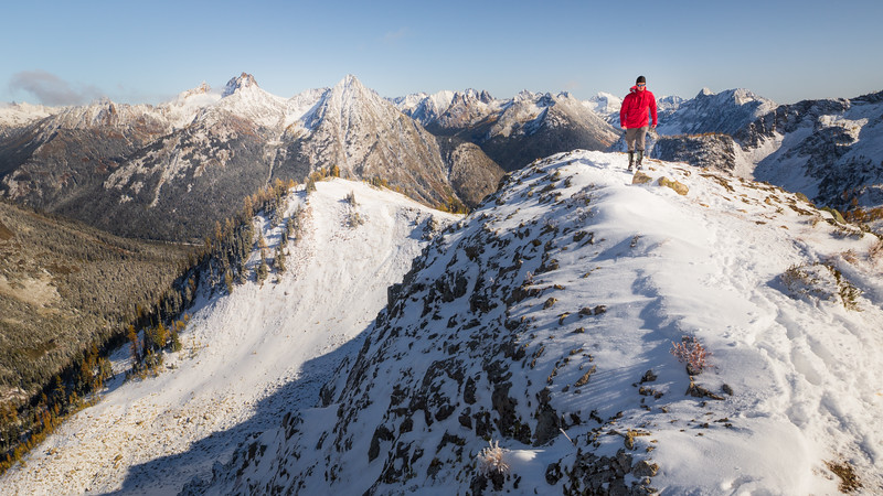 Rainy Pass. Maple Pass - Man in red jacket walking along snowy ridge towards camera, view towards Washington Pass