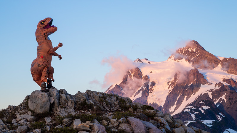 Whatcom, Artist Point - Man in t-rex costume posing in front of Mt Shuksan at twilight