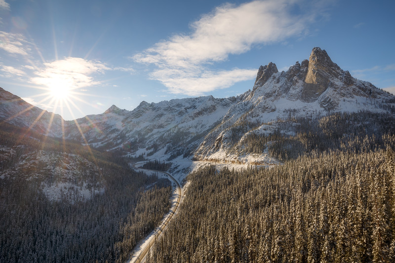 Washington Pass, Overlook - Liberty Bell and hairpin turn in snow with sun star